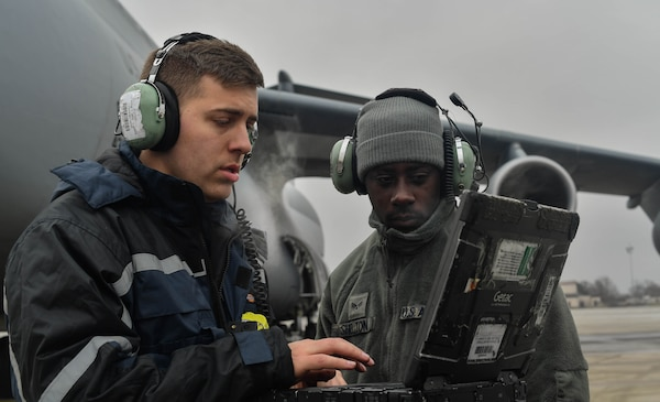 Staff Sgt. Zachary Rodewig, 721st Aircraft Maintenance Squadron C-5 Galaxy crew chief, explains the different aspects of maintenance for a C-5 aircraft to Senior Airman Earl Shelton, 721st AMXS aerospace maintenance technician, at Ramstein Air Base, Germany, Jan. 24, 2017. All Airmen within the 721st AMXS must be qualified on C-17 Globemaster III and C-5 aircraft. On average, the 721st AMXS inspects, services, and repairs 30 aircraft in a single day, as part of the 521st Air Mobility Operations Wing at Ramstein. (U.S. Air Force photo by Senior Airman Tryphena Mayhugh)