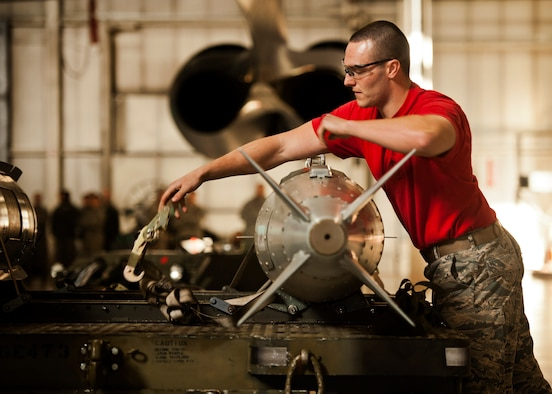 Senior Airman Nicholas George, 23rd Aircraft Maintenance Unit weapons load crew member, removes a strap from an inert GBU-31 at Minot Air Force Base, N.D., Jan. 20, 2017. The 23rd and 69th AMU competed in a timed bomb load as a part of the Load Crew of the Quarter competition. (U.S. Air Force photo/Airman 1st Class J.T. Armstrong)