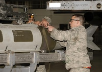 Staff Sgt. Eric Hathaway, 69th Aircraft Maintenance Unit weapons load crew chief, and Senior Airman Philip Johnson, 69th AMU weapons load crew member, strap an inert munition in place during the 5th Bomb Wing Load Crew of the Quarter competition in Dock 7 at Minot Air Force Base, N.D., Jan. 20, 2017. Hathaway and Johnson, assigned to the 5th Aircraft Maintenance Squadron, represented the 69th Air Maintenance Unit during the competition. (U.S. Air Force photo/Airman 1st Class Alyssa M. Akers)