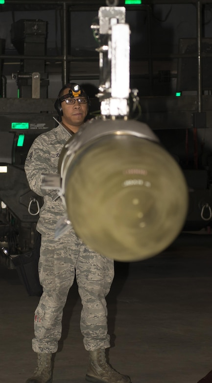 Senior Airman Philip Johnson, 69th Aircraft Maintenance Unit weapons load crew member, helps position an inert munition onto another machine during the 5th Bomb Wing Load Crew of the Quarter competition in Dock 7 at Minot Air Force Base, N.D., Jan. 20, 2017. Load crew members must maintain proficiency in 17 different types of munitions. (U.S. Air Force photo/Airman 1st Class Alyssa M. Akers)