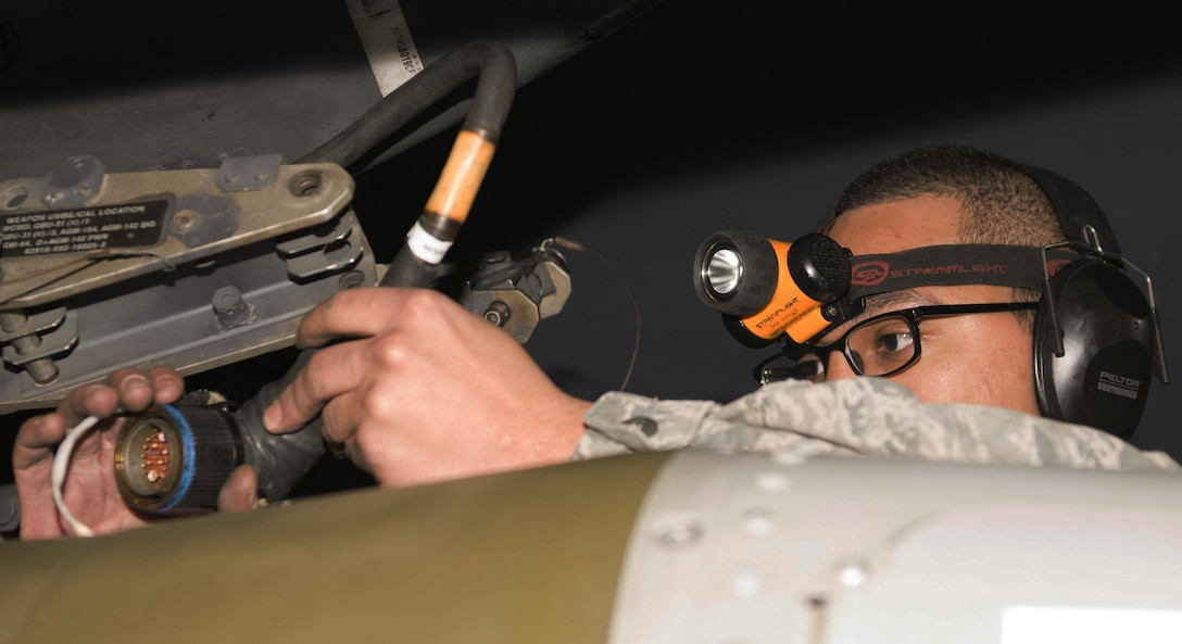 Senior Airman Philip Johnson, 69th Aircraft Maintenance Unit weapons load crew member, locks an inert munition onto a B-52H Stratofortress during the 5th Bomb Wing Load Crew of the Quarter competition in Dock 7 at Minot Air Force Base, N.D., Jan. 20, 2017. The 23rd and 69th AMU competed in a timed bomb load as a part of the Load Crew of the Quarter competition. (U.S. Air Force photo/Airman 1st Class Alyssa M. Akers)