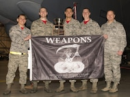 The weapons load crew representing the 23rd Aircraft Maintenance Unit in the 5th Bomb Wing Load Crew of the Quarter competition hold their award for winning the 5th Bomb Wing Load Crew of the Quarter competition in Dock 7 at Minot Air Force Base, N.D., Jan. 20, 2017. The competition was comprised of four parts: dress and appearance, a loader's knowledge test, toolbox inspection and the timed bomb load. (U.S. Air Force photo/Airman 1st Class Alyssa M. Akers)