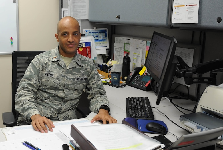 Second Lt. Ashenafi Asega, 22nd Medical Support Squadron TRICARE operations and patient administration flight commander sits at his desk, Nov. 4, 2016, at McConnell Air Force Base, Kan. Asega left Ethiopia to come to the United States when he was 22 years old to pursue an education and later joined the U.S. Air Force. (U.S. Air Force photo/Senior Airman Tara Fadenrecht)
