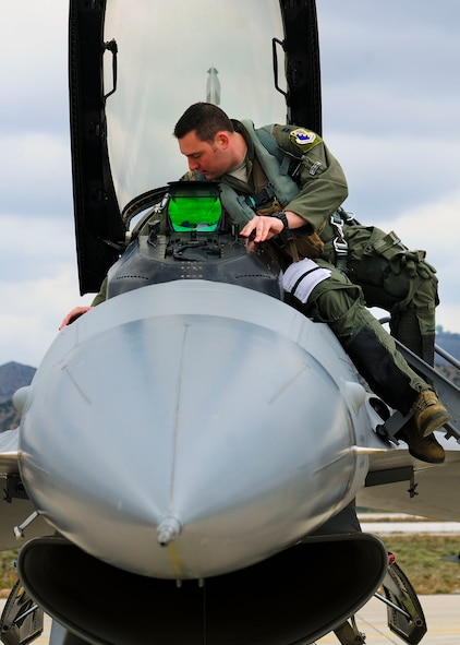 Capt. Kirk Devine, 555th Fighter Squadron F-16 Fighting Falcon pilot from Aviano Air Base, Italy prepares to enter his jet cockpit during a flying training deployment at Souda Bay, Greece on Jan. 23, 2016. Fourteen Aviano F-16s, one KC-135 Stratotanker from the Arizona Air National Guard's 161st Air Refueling Wing and 280 Airmen deployed to Souda Bay to train with Greece's Hellenic air force for the two week FTD, scheduled from Jan. 20 to Feb. 3. (U.S. Air Force photo by Staff Sgt. Austin Harvill)