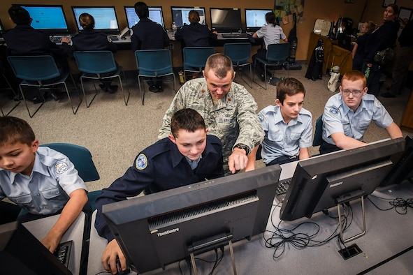 Maj. Trevor Cook, ICBM Systems Directorate Cyber Division deputy chief, mentors cadets at the Utah Military Academy, Riverdale, Utah, Jan. 5. The cadets – from the left: Cadet Airman Basic James Gill, Cadet Airman 1st Class Donaven Ellis, Cadet Airman Basic Jacob Hite and Cadet Airman Basic Caleb Gerhardt – are participating in Cyber Patriot IX, an annual competition for middle- and high-school students designed to prepare them for careers in cybersecurity and STEM (science, technology, engineering, and mathematics) disciplines. (U.S. Air Force photo by Paul Holcomb)