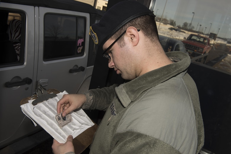 Senior Airman Gary Terrio, a 5th Security Forces Squadron installation entry controller, checks an I.D. card at Minot Air Force Base, N.D., Jan. 19, 2017. All security forces Airmen must first pass a test to be allowed to check the I.D.s of base visitors. (U.S. Air Force photo/Airman 1st Class Alyssa M. Akers)