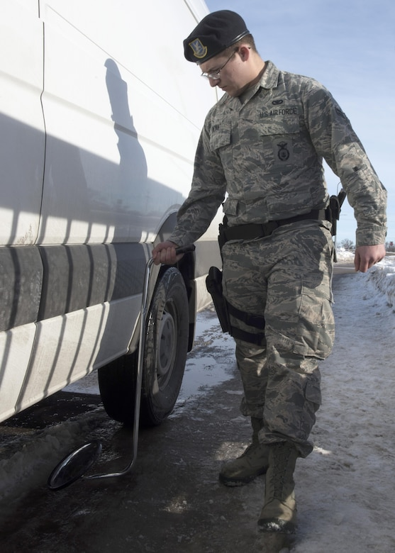 Airman 1st Class Michael Wyant, 5th Security Forces Squadron installation entry controller, uses a mirror to inspect the bottom of a vehicle at Minot Air Force Base, N.D., Jan. 19, 2017. Vehicle inspections are crucial to the safety of the military installation. (U.S. Air Force photo/Airman 1st Class Alyssa M. Akers)
