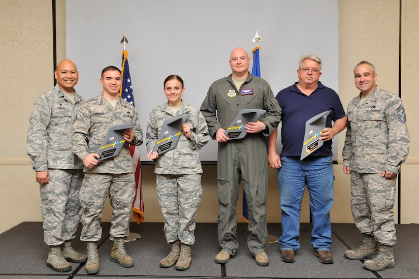 Col. Jimmy Canlas, left, 437th Airlift Wing (AW) commander, and Chief Master Sgt. Kristopher Berg, right, 437th AW command chief, congratulate the 437th AW Fourth Quarterly Award winners during a quarterly awards ceremony at the Joint Base Charleston Air Base Club, Jan. 23, 2016.
