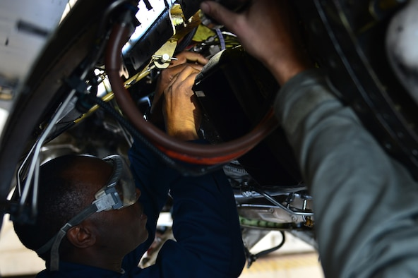 U.S. Air Force Tech. Sgt. Isaiah English, 20th Aircraft Maintenance Squadron tactical aircraft maintainer, examines the wiring under an F-16CM Fighting Falcon at Shaw Air Force Base, S.C., Jan. 25, 2017. English examined the wire to ensure that it was within safety regulations and made repairs where needed. (U.S. Air Force photo by Airman 1st Class Christopher Maldonado)