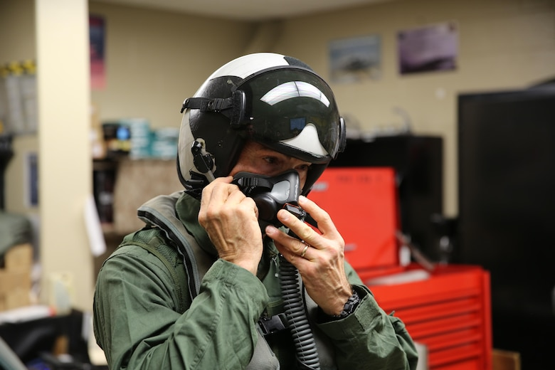 Maj. Gen. John Love buckles his oxygen mask before flying with Marine Attack Training Squadron 203, Marine Aircraft Group 14, 2nd Marine Aircraft Wing aboard Marine Corps Air Station Cherry Point, Jan. 27, 2017. Love strapped into one of the squadron's AV-8B Harriers for the first time in his career. Love's visit helped strengthen the relationship between the ground and air combat elements while showcasing the capabilities of the aircraft firsthand. Love is the commanding general of the 2nd Marine Division. (U.S. Marine Corps photo by Lance Cpl. Cody Lemons/Released)