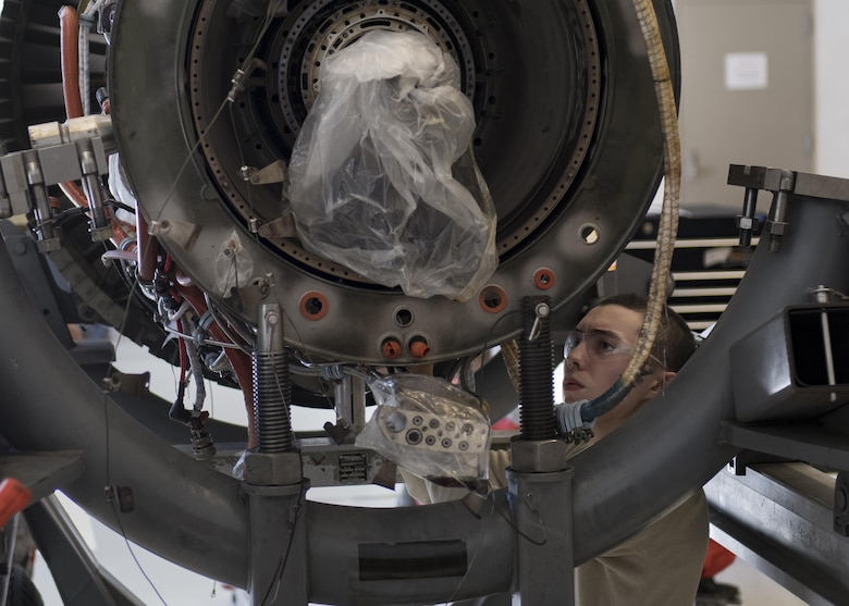 Airman 1st Class Anthony Guevara, 23d Component Maintenance Squadron propulsion technician, reaches into the underside of a TF-34 engine used in A-10C Thunderbolt lls, Jan. 25, 2017, at Moody Air Force Base, Ga. The 23d CMS is currently involved in an event aimed at decreasing the scheduled 28 days it takes to disassemble, repair and reassemble the TF-34 engine. (U.S. Air Force photo by Airman 1st Class Daniel Snider)