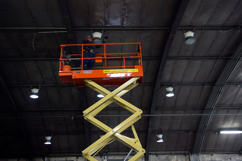 """Mark Butler, local civilian contractor, installs a light fixture in the under construction """"Hush House 2,"""" Jan. 23, 2017, at Moody Air Force Base, Ga. All services for the complete overhaul of the facility including the structure, intake and exhaust systems and test systems is slated to finish by approximately April 2017. (U.S. Air Force photo by Airman 1st Class Greg Nash)"""