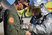 Sgt. Aaron Mack adjusts Cpl. Miguel Avalos's gear during a live fire training event on Marine Corps Air Station New River, N.C., Jan. 19, 2017. The training used propane and piping to simulate fires on the interior and exterior of an aircraft. Mack is an assistant section leader with Marine Corps Air Station New River's Aircraft Rescue Firefighting division. Avalos is a rescueman with Marine Corps Air Station New River's Aircraft Rescue Firefighting division. (U.S. Marine Corps photo by Cpl. Melodie Snarr)