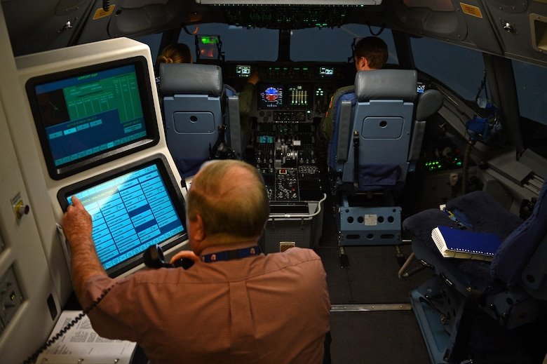 Robert Callahan, C-17 instructor pilot, observes Capt. Brittany Bean (left) and Capt. Hatton Updike (right), both 4th Airlift Squadron C-17 Globemaster III pilots, during a quarterly training session in a C-17 Globemaster III simulator Jan. 26, 2017 at Joint Base Lewis-McChord, Wash. Using the simulator gives pilots an opportunity to practice on things pilots can't accomplish in the aircraft, but with a great level of realism. (U.S. Air Force photo/Senior Airman Divine Cox)
