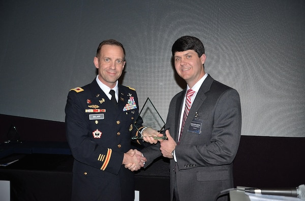 Justin McDonald (Right), lead engineer for USACE Mobile Civil Works, accepts the 2017 Mobile Area Council of Engineers (MACE) 'Young Engineer of the Year' award from District Commander Col. James DeLapp Jan. 26 at the Gulf Coast Exploreum Science Center in Mobile, Ala. The award is handed out to an engineer who is under the age of 35 and who demonstrates leadership in their professional lives and in the community.