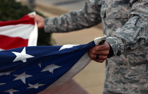 An Airman holds the U.S. flag during retreat on Maxwell Air Force Base, Ala., Jan. 26, 2017. All ALS students participate in reveille and retreat every day as part of their duties during the five-week leadership course. (U.S. Air Force photo/Senior Airman Tammie Ramsouer)