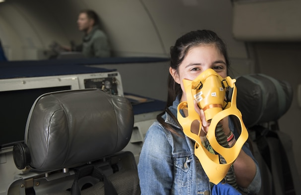 Skylie Carreno, Ryukyu Middle School student, tries on an oxygen mask onboard an E-3 Sentry Jan. 27, 2017, at Kadena Air Base, Japan. Ryukyu Middle School students were invited to the 961st Airborne Air Control Squadron Squad to learn about their mission on Kadena Air Base. (U.S. Air Force photo by Senior Airman Omari Bernard/Released)