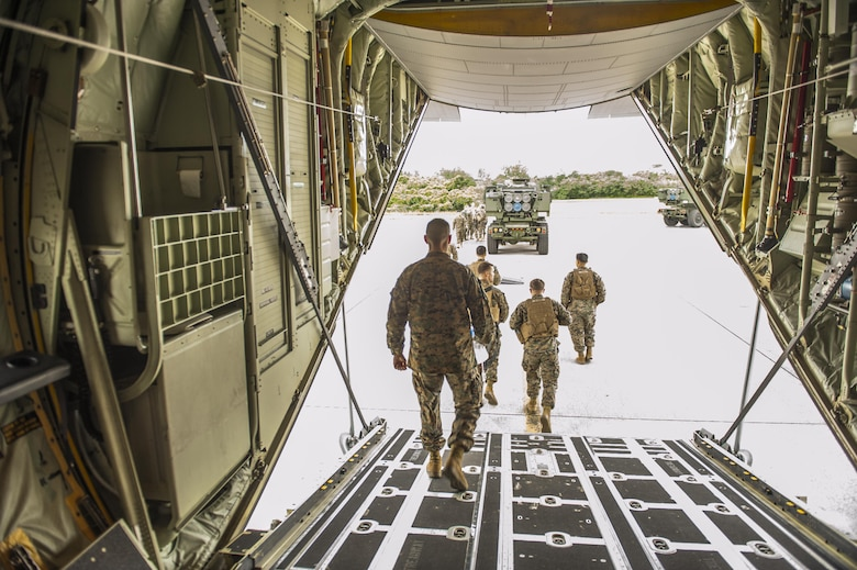 U.S. Marine Corps Marines with the 5th Battalion, 11th Marines, exit a C-130 Hercules after a briefing prior to training with 17th Special Operations Squadron Airmen on the flightline at Kadena Air Base, Japan, Jan. 23, 2017. Opportunities to train with members of other military branches allow for aircrew to learn about unfamiliar systems and types of operations. (U.S. Air Force photo by Airman 1st Class Nick Emerick/Released)