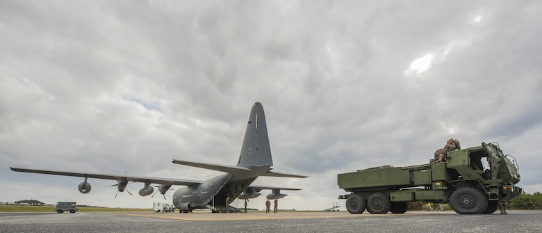U.S. Marine Corps Marines with the 5th Battalion, 11th Marines, and U.S. Air Force Airmen with the 17th Special Operations Squadron, load a high mobility artillery rocket system onto a C-130 Hercules on the flightline at Kadena Air Base, Japan, Jan. 23, 2017. A HIMAR is a self-propelled artillery piece mounted on a 5-ton chassis with a rocket pod on the back that shoots rockets and missiles. (U.S. Air Force photo by Airman 1st Class Nick Emerick/Released)
