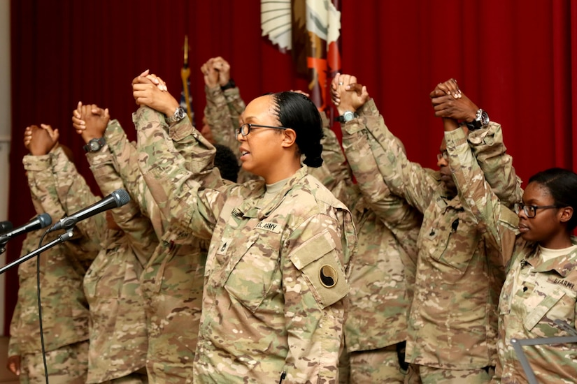 Soldiers hold hands after a quartet sing a medley in celebration of the life of Dr. Martin Luther King Jr. during an observance at Camp Arifjan, Kuwait, Jan. 12, 2016. The observance included the singing of the national anthem, a poem recital an a cappella quartet, and key note speakers.