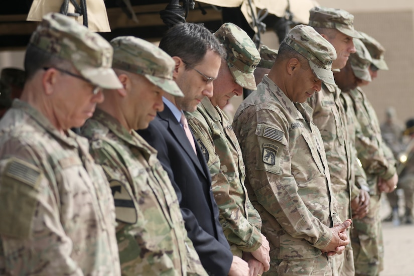 The official party from U.S. Army Central and the 29th Infantry Division pause during the invocation at a Transfer of Authority ceremony to place the 29th Inf. Div. as the new command for Task Force Spartan at Camp Arifjan, Kuwait, Dec. 19, 2016. (U.S. Army photo by Sgt. Brandon Hubbard)