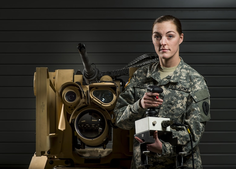 Spc. Rachel Schulte, a U.S. Army Reserve Soldier with the 354th Military Police Company, of St. Louis, Missouri, poses with a Common Remotely Operated Weapon Station (CROWS), at Fort Chaffee, Arkansas, Jan. 26. The CROWS is a remote-controlled system compatible with four major crew-serve weapons, and it was developed to keep gunners safe within the vehicle while engaging enemy targets. (U.S. Army Reserve photo by Master Sgt. Michel Sauret)