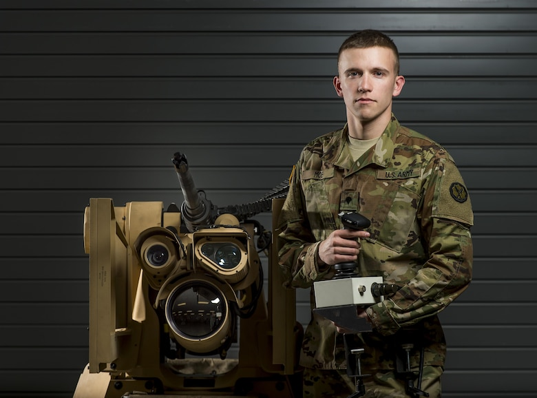 Spc. Ethan Moe, a U.S. Army Reserve Soldier with the 800th Military Police Company, of Little Rock, Arkansas, poses with the Common Remotely Operated Weapon Station (CROWS), at Fort Chaffee, Arkansas, Jan. 26. The CROWS is a remote-controlled system compatible with four major crew-serve weapons, and it was developed to keep gunners safe within the vehicle while engaging enemy targets. (U.S. Army Reserve photo by Master Sgt. Michel Sauret)