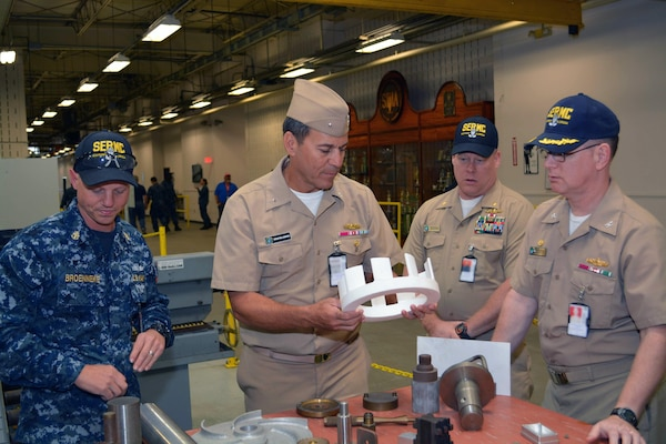 Machinery Repair Technician Chief Jason Broenneke, Capt. Dave Gombas and Lt. Cmdr. Keith Foster show examples of fabricated shipboard materiel to Rear Adm. Stephen F. Williamson. The examples were all fabricated by Sailors at Southeast Regional Maintenance Center (SERMC).  Rear Adm. Williamson toured the different production lines, shops and labs present at SERMC.
