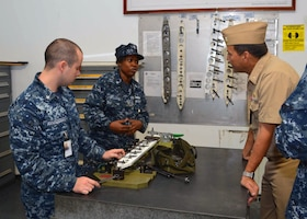 Gas Turbine Systems Technician (Maintenance) 2nd Class Matthew Armstrong and Gas Turbine Systems Technician (Maintenance) Carla Williams explain how they perform maintenance on replacement parts for ship repairs to Rear Admiral Stephen F. Williamson.  Rear Adm. Williamson was onboard to engage key staff on ship maintenance and workload.