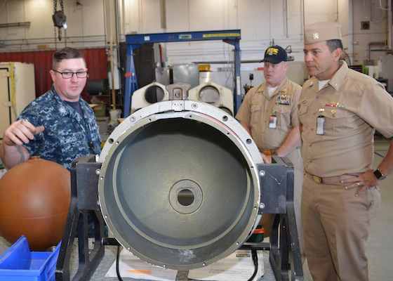 Machinist's Mate 1st Class Earl Riggs discusses some of the maintenance involved with torpedo tubes at Southeast Regional Maintenance Center (SERMC). Williamson served as the Combat Systems Repair Officer at SERMC during a previous tour of duty.