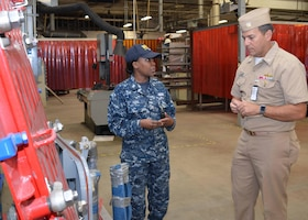 Damage Controlman 1st Class Fungai Diura explains to Rear Adm. Stephen F. Williamson how damaged watertight doors are repaired at Southeast Regional Maintenance Center. Rear Adm. Williamson is the Director for Fleet Maintenance, United States Pacific Fleet.