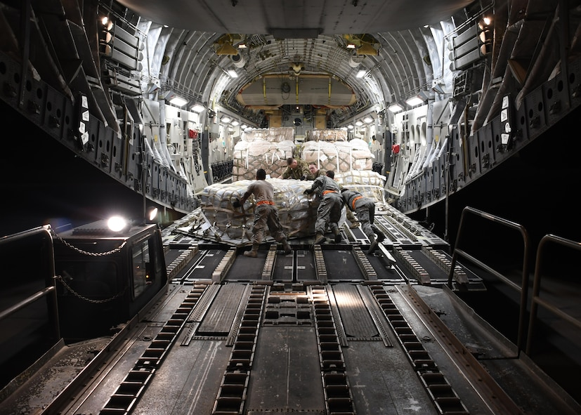 U.S. Air Force Airmen from the 8th Expeditionary Air Mobility Squadron and 816th Expeditionary Airlift Squadron load cargo onto a C-17 Globemaster III at Al Udeid Air Base, Qatar, Dec. 23, 2016. After loading the cargo, the two squadrons secure it so there are no issues while in flight. In 2016, the 816th EAS flew more than 2,400 missions, moving nearly 102,000 tons of cargo and almost 120,000 passengers. (U.S. Air Force photo by Senior Airman Miles Wilson)