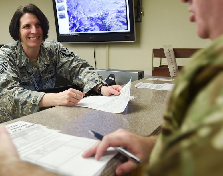 U.S. Air Force Tech. Sgt. Ashley Weatherly, Red Flag 17-1 weather forecaster from the 1st Operational Support Squadron at Joint Base Langley-Eustis, Va., answers a coalition partner's questions about forecasts at Nellis Air Force Base, Nev., Jan. 23, 2017. The exercise's weather forecasters prepare products that determine the ability to safely accomplish air-to-air combat training missions during the exercise. (U.S. Air Force photo by Staff Sgt. Natasha Stannard)