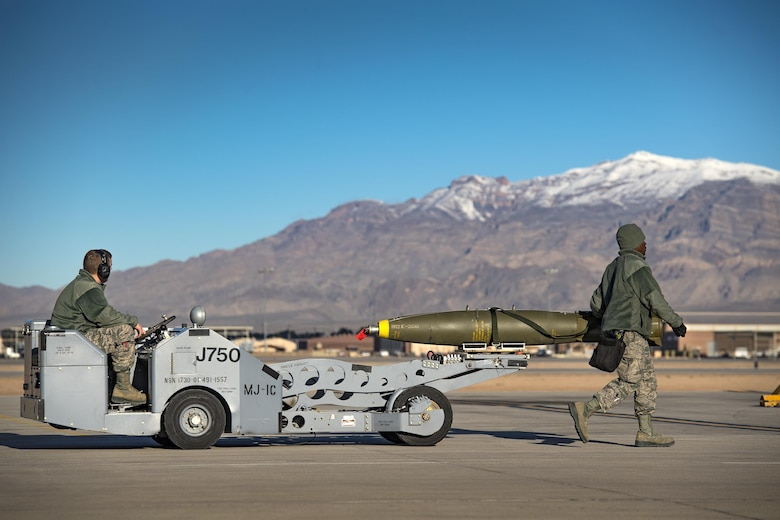 Airman First Class Connor McDonald, left, and Staff Sgt. Tayrell Washington, both 74th Aircraft Maintenance Unit weapons load team members, use an MJ-1C bomb lift to transport a Mark 82 general purpose bomb during Green Flag-West 17-03, Jan. 24, 2017, at Nellis Air Force Base, Nev. Weapons Airmen enabled joint force training during the two-week exercise by loading weapons, inspecting jets and maintaining munitions systems. Some of the live munitions included the Mark 82 and 84 general purpose bombs, high-explosive incendiary 30mm rounds and the 500 pound GBU-12 Paveway II laser-guided bomb. (U.S. Air Force photo by Staff Sgt. Ryan Callaghan)