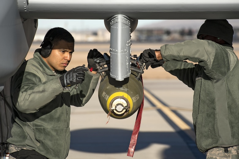 Airman First Class Carlos Quintanilla, left, and Staff Sgt. Tayrell Washington, 74th Aircraft Maintenance Unit weapons load team members, secure a Mark 82 general purpose bomb to the bottom of an A-10C Thunderbolt II during Green Flag-West 17-03, Jan. 24, 2017, at Nellis Air Force Base, Nev. Weapons Airmen enabled joint force training during the two-week exercise by loading weapons, inspecting jets and maintaining munitions systems. Some of the live munitions included the Mark 82 and 84 general purpose bombs, high-explosive incendiary 30mm rounds and the 500 pound GBU-12 Paveway II laser-guided bomb. (U.S. Air Force photo by Staff Sgt. Ryan Callaghan)