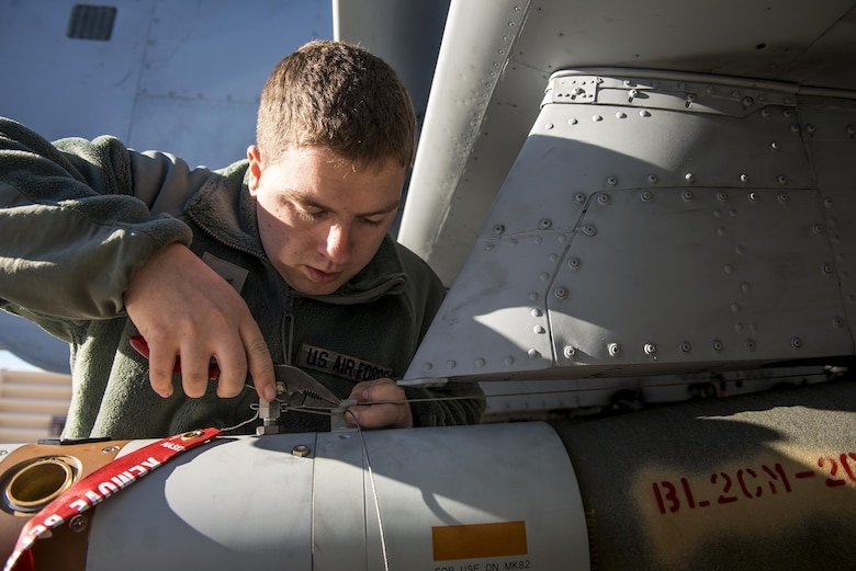 Airman First Class Connor McDonald, 74th Aircraft Maintenance Unit weapons load team member, installs an arming wire on a GBU-12 Paveway II laser-guided bomb during Green Flag-West 17-03, Jan. 24, 2017, at Nellis Air Force Base, Nev. Weapons Airmen enabled joint force training during the two-week exercise by loading weapons, inspecting jets and maintaining munitions systems. Some of the live munitions included the Mark 82 and 84 general purpose bombs, high-explosive incendiary 30mm rounds and the 500 pound GBU-12 Paveway II laser-guided bomb. (U.S. Air Force photo by Staff Sgt. Ryan Callaghan)