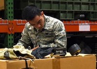 U.S. Air Force Airman Joerimer Collado, an individual protective equipment (IPE) specialist assigned to the 509th Logistics Readiness Squadron (LRS), creates an inventory list for disposition items at Whiteman Air Force Base, Mo., Jan. 17, 2017. When items are no longer needed in the IPE shop they are put into crates to be transferred to another facility. (U.S. Air Force photo by Senior Airman Danielle Quilla)