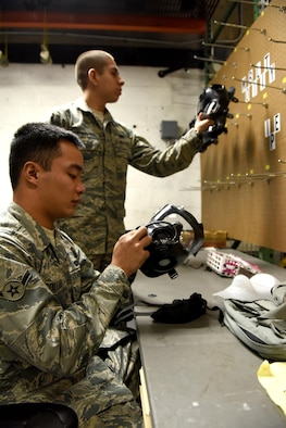 U.S. Air Force Airman Joerimer Collado, left, and Airman Aleandro Pust Cunibertti, individual protective equipment (IPE) specialists assigned to the 509th Logistics Readiness Squadron, disassemble gas masks at Whiteman Air Force Base, Mo., Jan. 18, 2017. Once an individual turns in their protective gear, the gas masks are taken apart to be sterilized and inspected. (U.S. Air Force photo by Senior Airman Danielle Quilla)