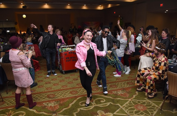 Senior Airman Natalie Malloy, 81st Inpatient Operations Squadron medical technician, and Staff Sgt. Quaci Allen, 81st Surgical Operations Squadron medical technician, dance down the aisle during a Mardi Gras float contest during the 29th Annual Krewe of Medics Mardi Gras Ball at the Bay Breeze Event Center Jan. 28, 2017, on Keesler Air Force Base, Miss. The Krewe of Medics hosts a yearly ball to give Keesler Medical Center personnel a taste of the Gulf Coast and an opportunity to experience a traditional Mardi Gras. The theme for this year's ball was Blast From The Past. (U.S. Air Force photo by Kemberly Groue)