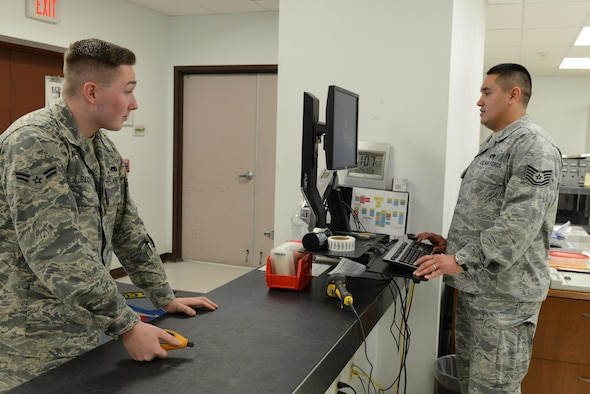 Airman 1st Class Jordan Barker, 56th Component Maintenance Squadron precision measurement equipment laboratory technician, and Tech. Sgt. Miguel Ruiz, 56th CMS noncommissioned officer-in-charge of production control, simulate a test measurement diagnostic equipment procedure Jan. 24, 2017, at Luke Air Force Base, Ariz. The TMDE is used to create a job control number which is the beginning stages of getting an item recalibrated.(U.S. Air Force photo by Airman 1st Class Pedro Mota)
