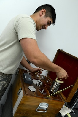 Senior Airman Donald Area, 56th Component Maintenance Squadron precision measurement equipment laboratory technician, lifts class 1 weights with prongs for a simulated weight measurement Jan. 24, 2017, at Luke Air Force Base, Ariz. The high accuracy weights are used to calibrate high accuracy scales.(U.S. Air Force photo by Airman 1st Class Pedro Mota)