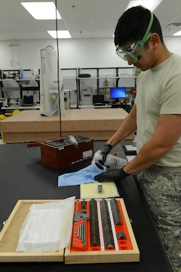 Senior Airman Donald Area, 56th Component Maintenance Squadron precision measurement equipment laboratory technician, cleans gauge blocks with ethyl alcohol Jan. 24, 2017, at Luke Air Force Base, Ariz. The gauge blocks are used to calibrate micrometers for fabrication flight spacing or depth measurements on an aircraft. (U.S. Air Force photo by Airman 1st Class Pedro Mota)