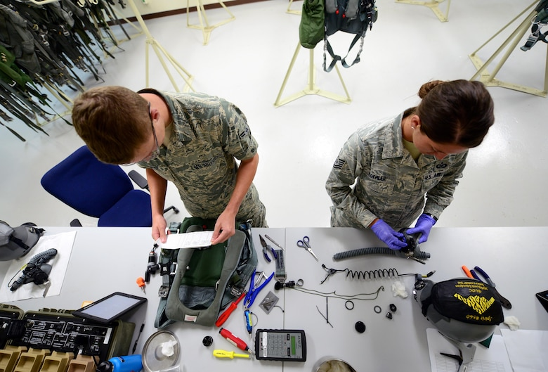 U.S. Air Force Tech. Sgt. Suzanne Koehler, an aircrew flight equipment technician assigned to the 131st Operations Support Flight, and Airman 1st Class Timothy Doyle, an aircrew flight equipment apprentice assigned to the 509th Operations Support Squadron, take apart aircrew equipment to ensure all components are correctly functioning at Andersen Air Force Base, Guam, Jan. 24, 2017. Bomber missions familiarize aircrew with airbases and operations in different Geographic Combatant Commands. (U.S. Air Force photo by Airman 1st Class Jazmin Smith)
