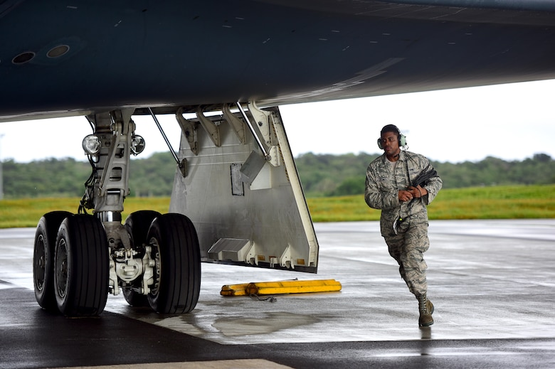 U.S. Air Force Senior Airman Dez Starkes, a crew chief assigned to the 509th Aircraft Maintenance Squadron, runs to the other side of a B-2 Spirit to remove chocks from the wheels prior to takeoff at Andersen Air Force Base, Guam, Jan. 12, 2017. Strategic bomber missions enhance the readiness and training necessary to respond to any potential crisis or challenge across the globe. (U.S. Air Force photo by Airman 1st Class Jazmin Smith)
