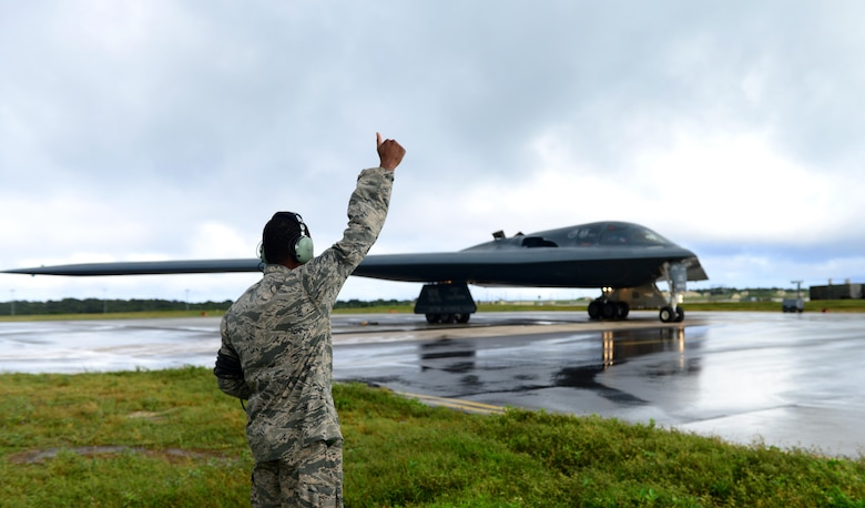 U.S. Air Force Senior Airman Dez Starkes, a crew chief assigned to the 509th Aircraft Maintenance Squadron, signals to the mission commander that he is clear and free to move forward at Andersen Air Force Base, Guam, Jan. 12, 2017. Strategic bomber missions enhance the readiness and training necessary to respond to any potential crisis or challenge across the globe. (U.S. Air Force photo by Airman 1st Class Jazmin Smith)
