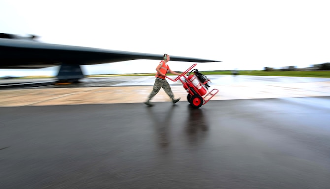 U.S. Air Force Senior Airman Richard Huartson, a crew chief assigned to the 509th Aircraft Maintenance Squadron, walks the fire extinguisher off the parkway prior to a U.S. Air Force B-2 Spirit aircraft takeoff at Andersen Air Force Base, Guam, Jan. 12, 2017. Close to 200 Airmen from Whiteman Air Force Base, Mo., and Barksdale Air Force Base, La., deployed to Andersen AFB, in support of U.S. Strategic Command Bomber and Deterrence missions. USSTRATCOM bomber missions familiarize aircrew with airbases and operations in different Geographic Combatant Commands. (U.S. Air Force photo by Tech. Sgt. Andy M. Kin)