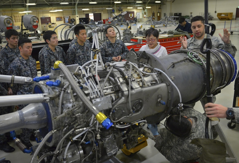 Staff Sgt. Synard Bert, 374th Maintenance Squadron propulsion flight propulsion journeyman, explains the structure of a C-130H Hercules engine to Japan Air Self Defense Force maintenance officers-in-training at Yokota Air Base, Japan, Jan. 25, 2017. The officers-in-training learned about how Yokota maintenance works in order to strengthen ties and improve bilateral operations. (U.S. Air Force photo by Senior Airman Elizabeth Baker)