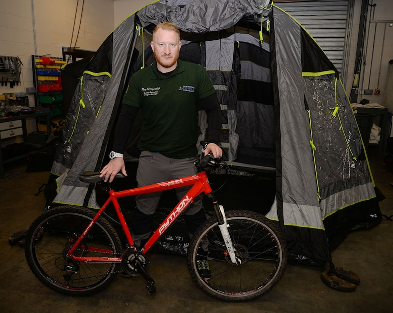 Ray Hoogendijk, 100th Force Support Squadron Outdoor Recreation program manager, shows off one of the mountain bikes and inflatable tents which can be rented from outdoor recreation Jan. 30, 2017, on RAF Mildenhall, England. The center has a wide array of items for outdoor activities available for rent, and organizes outdoor activities such as hiking, mountain biking, mountain climbing and water sports. (U.S. Air Force photo by Karen Abeyasekere)