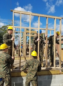 On January 24, 2017 at Courthouse Bay, Camp Lejeune, N.C., Marines attached to Combat Engineer Officer course 2-17 (CEO 2-17) install a prefabricated wood frame wall as part of the practical application portion of their lesson on vertical construction. CEO students learn how to plan and construct single-story structures during this period of instruction.  Pictured from left to right are Second Lieutenants Wesley Rathwick, Chase Alexanian, Carlos Perez, Cody Murphy, and Mitchell Bottini.