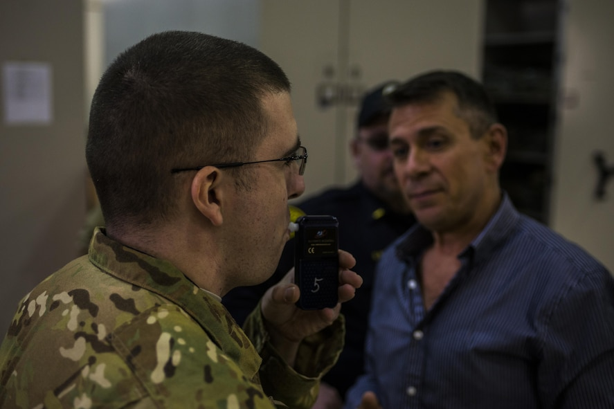 Gary Rhode, 27th Special Operations Security Forces Squadron training superintendent, right, watches as a participant conducts a breathalyzing test during Standardized Field Sobriety Test training for 27th SOSFS members Jan. 25, 2017, at Cannon Air Force Base, N.M. Rhode led twelve Security Forces members in his National Highway Traffic Safety Administration 24-hour class on SFSTs. (U.S. Air Force photo by Senior Airman Luke Kitterman/Released)